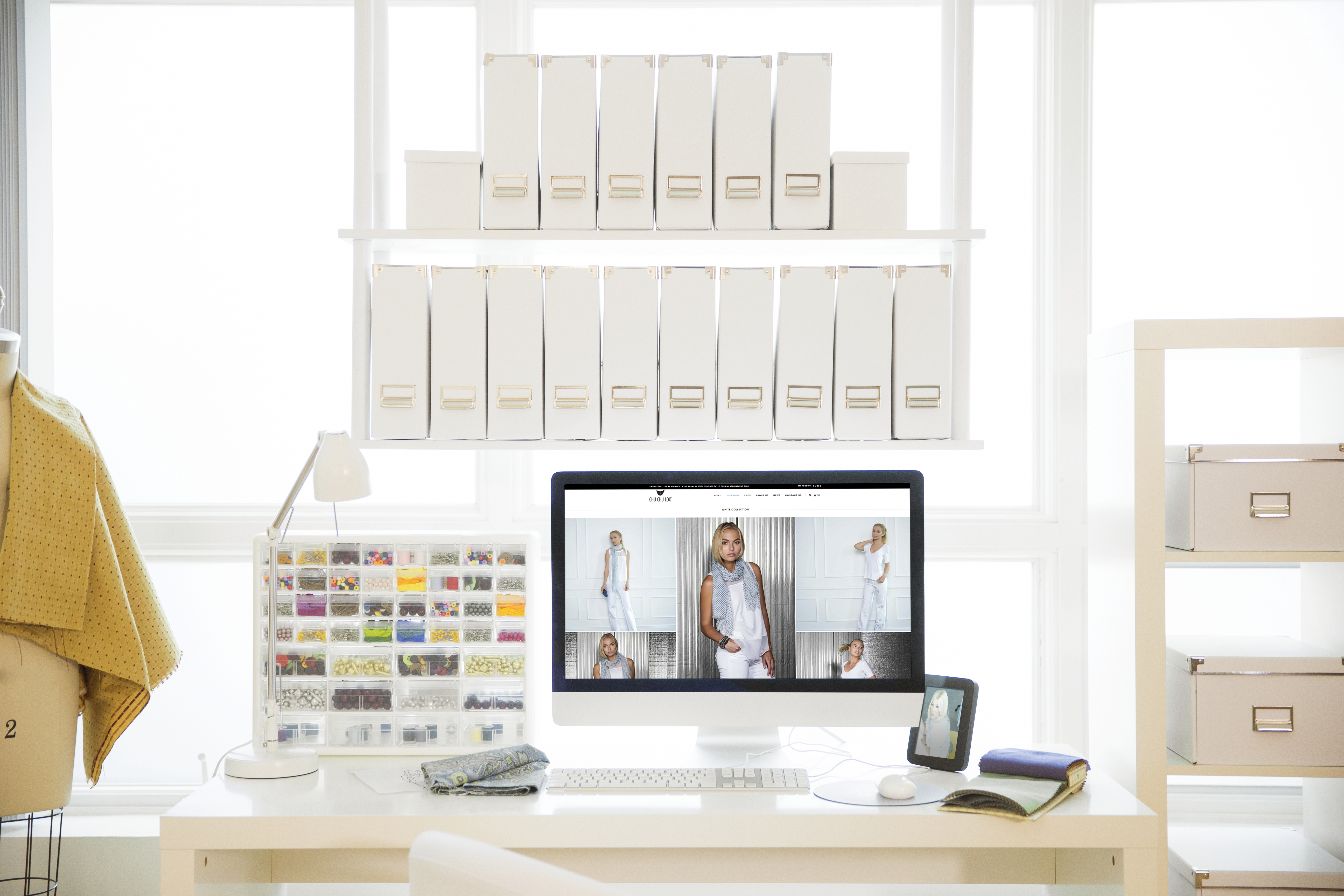 Design studio with fashion illustration designs on computer monitor with mannequin, fabric samples and no people.